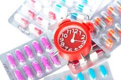 Κόκκινο ξυπνητήρι και ιατρικό πακέτο φουσκαλών Στοκ εικόνα με δικαίωμα ελεύθερης χρήσης