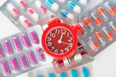 Κόκκινο ξυπνητήρι και ιατρικό πακέτο φουσκαλών Στοκ Φωτογραφίες