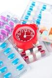 Κόκκινο ξυπνητήρι και ιατρικό πακέτο φουσκαλών Στοκ εικόνες με δικαίωμα ελεύθερης χρήσης