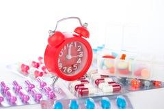 Κόκκινο ξυπνητήρι και ιατρικό πακέτο φουσκαλών Στοκ Φωτογραφία