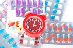 Κόκκινο ξυπνητήρι και ιατρικό πακέτο φουσκαλών Στοκ Εικόνες