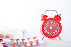 Κόκκινο ξυπνητήρι και ιατρικό πακέτο φουσκαλών Στοκ φωτογραφία με δικαίωμα ελεύθερης χρήσης