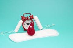 Κόκκινο ξυπνητήρι, ονειροπόλος πτώση αίματος τσιγγελακιών χαμόγελου, καθημερινά εμμηνορροϊκά μαξιλάρι και tampons Υγειονομική υγι στοκ φωτογραφία με δικαίωμα ελεύθερης χρήσης