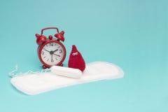 Κόκκινο ξυπνητήρι, ονειροπόλος πτώση αίματος τσιγγελακιών χαμόγελου, καθημερινά εμμηνορροϊκά μαξιλάρι και tampon Υγειονομική υγιε στοκ εικόνες