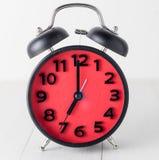 Κόκκινο ξυπνητήρι στην άσπρη επιτραπέζια καθιέρωση σε 7 Στοκ Εικόνες