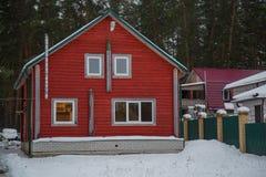 Κόκκινο ξύλινο χειμερινό χιονώδες τοπίο σπιτιών Στοκ φωτογραφίες με δικαίωμα ελεύθερης χρήσης