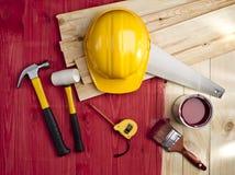 Κόκκινο ξύλινο πάτωμα με μια βούρτσα, ένα χρώμα, ένα σφυρί και ένα κράνος Στοκ φωτογραφία με δικαίωμα ελεύθερης χρήσης