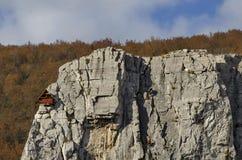 Κόκκινο ξύλινο σπίτι ορειβατών στους βράχους Lakatnik και τον αλπικό ορειβάτη, defile ποταμών Iskar, επαρχία της Sofia Στοκ εικόνα με δικαίωμα ελεύθερης χρήσης