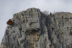 Κόκκινο ξύλινο σπίτι ορειβατών στους βράχους Lakatnik και τον αλπικό ορειβάτη, defile ποταμών Iskar, επαρχία της Sofia Στοκ Φωτογραφία