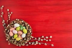 κόκκινο Πάσχας ανασκόπησης Στεφάνι ιτιών Πάσχας και ζωηρόχρωμα αυγά Πάσχας στο κόκκινο υπόβαθρο Τοπ άποψη, διάστημα αντιγράφων Στοκ Εικόνες