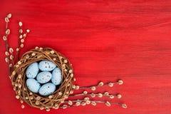 κόκκινο Πάσχας ανασκόπησης Στεφάνι ιτιών Πάσχας και ζωηρόχρωμα αυγά Πάσχας στο κόκκινο υπόβαθρο Τοπ όψη Στοκ εικόνα με δικαίωμα ελεύθερης χρήσης