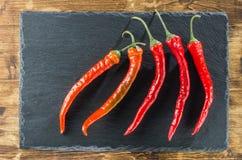 Κόκκινο πέντε - καυτά πιπέρια διαγώνια στα πλαίσια της πλάκας Στοκ Φωτογραφία