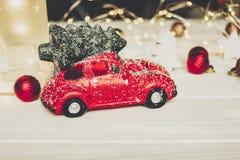 Κόκκινο παιχνίδι αυτοκινήτων με το χριστουγεννιάτικο δέντρο στις τοπ και απλές διακοσμήσεις στο W Στοκ Εικόνες
