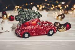 Κόκκινο παιχνίδι αυτοκινήτων με το χριστουγεννιάτικο δέντρο στις τοπ και απλές διακοσμήσεις στο W Στοκ Φωτογραφίες