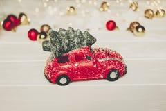 Κόκκινο παιχνίδι αυτοκινήτων με το χριστουγεννιάτικο δέντρο στις τοπ και απλές διακοσμήσεις στο W Στοκ εικόνα με δικαίωμα ελεύθερης χρήσης