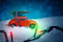 Κόκκινο παιχνίδι αυτοκινήτων που φέρνει ένα χριστουγεννιάτικο δέντρο, φω'τα Χριστουγέννων στο φ Στοκ φωτογραφίες με δικαίωμα ελεύθερης χρήσης