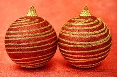 Κόκκινο παιχνίδι Χριστουγέννων δύο με τα χρυσά λωρίδες σε μια κόκκινη κινηματογράφηση σε πρώτο πλάνο υποβάθρου νέο έτος Χριστουγέ Στοκ Εικόνες