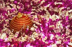 Κόκκινο παιχνίδι Χριστουγέννων με τα χρυσά λωρίδες σε μια ζωηρόχρωμη κινηματογράφηση σε πρώτο πλάνο υποβάθρου νέο έτος Χριστουγέν Στοκ φωτογραφία με δικαίωμα ελεύθερης χρήσης
