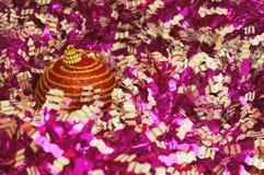 Κόκκινο παιχνίδι Χριστουγέννων με τα χρυσά λωρίδες σε μια ζωηρόχρωμη κινηματογράφηση σε πρώτο πλάνο υποβάθρου νέο έτος Χριστουγέν Στοκ Εικόνα