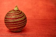 Κόκκινο παιχνίδι Χριστουγέννων με τα χρυσά λωρίδες σε μια κόκκινη κινηματογράφηση σε πρώτο πλάνο υποβάθρου νέο έτος Χριστουγέννων Στοκ Εικόνα