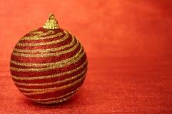 Κόκκινο παιχνίδι Χριστουγέννων με τα χρυσά λωρίδες σε μια κόκκινη κινηματογράφηση σε πρώτο πλάνο υποβάθρου νέο έτος Χριστουγέννων Στοκ φωτογραφία με δικαίωμα ελεύθερης χρήσης