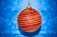 Κόκκινο παιχνίδι Χριστουγέννων με τα χρυσά λωρίδες σε μια μπλε κινηματογράφηση σε πρώτο πλάνο υποβάθρου νέο έτος Χριστουγέννων αν Στοκ Εικόνα
