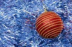 Κόκκινο παιχνίδι Χριστουγέννων με τα χρυσά λωρίδες σε μια μπλε κινηματογράφηση σε πρώτο πλάνο υποβάθρου νέο έτος Χριστουγέννων αν Στοκ φωτογραφίες με δικαίωμα ελεύθερης χρήσης