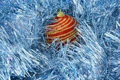 Κόκκινο παιχνίδι Χριστουγέννων με τα χρυσά λωρίδες σε μια μπλε κινηματογράφηση σε πρώτο πλάνο υποβάθρου νέο έτος Χριστουγέννων αν Στοκ φωτογραφία με δικαίωμα ελεύθερης χρήσης