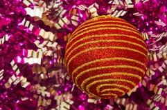 Κόκκινο παιχνίδι Χριστουγέννων με τα χρυσά λωρίδες σε μια κινηματογράφηση σε πρώτο πλάνο υποβάθρου νέο έτος Χριστουγέννων αν&alph Στοκ Φωτογραφία