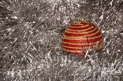 Κόκκινο παιχνίδι Χριστουγέννων με τα χρυσά λωρίδες στην κινηματογράφηση σε πρώτο πλάνο υποβάθρου νέο έτος Χριστουγέννων αν&alpha Στοκ Εικόνες