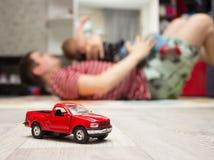 Κόκκινο παιχνίδι αυτοκινήτων, πατέρων και γιων παιχνιδιών στο υπόβαθρο Στοκ Εικόνες