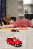 Κόκκινο παιχνίδι αυτοκινήτων, πατέρων και γιων παιχνιδιών στο υπόβαθρο Στοκ Φωτογραφίες