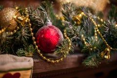 Κόκκινο παιχνίδι Χριστουγέννων μεταξύ των κομψών κλάδων και των χρυσών φω'των Η διάθεση της περιόδου Χριστουγέννων και διακοπών Στοκ Φωτογραφία