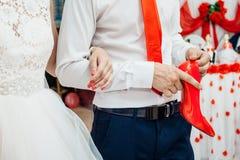 Κόκκινο παπούτσι νυφών ` s στα χέρια του συζύγου της Στοκ φωτογραφίες με δικαίωμα ελεύθερης χρήσης