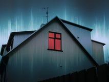 Κόκκινο παράθυρο σε ένα σπίτι τη νύχτα Στοκ Εικόνες