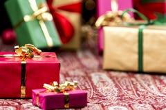 Κόκκινο παρόν μεταξύ άλλων δώρων και μπιχλιμπιδιών στοκ φωτογραφίες
