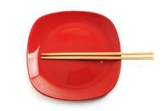 Κόκκινο πιάτο με τα κινεζικά ραβδιά Στοκ Φωτογραφίες