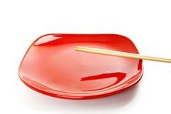 Κόκκινο πιάτο με τα κινεζικά ραβδιά Στοκ φωτογραφία με δικαίωμα ελεύθερης χρήσης