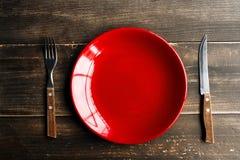Κόκκινο πιάτο στον πίνακα με το μαχαίρι και το δίκρανο Στοκ Φωτογραφίες