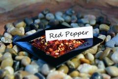 Κόκκινο πιπέρι σε ένα μικρό πιάτο με την ετικέτα Στοκ Φωτογραφίες