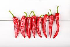 Κόκκινο πιπέρι τσίλι που βρίσκεται σε μια σειρά Στοκ Φωτογραφίες
