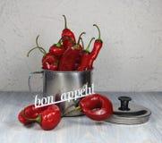 Κόκκινο πιπεριών σε μια κούπα μετάλλων με τις πτώσεις και την επιγραφή νερού bon appetit Στοκ Εικόνα