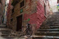 Κόκκινο ποδήλατο στην οδό μιας παλαιάς πέτρας λίγη πόλη στοκ εικόνα με δικαίωμα ελεύθερης χρήσης