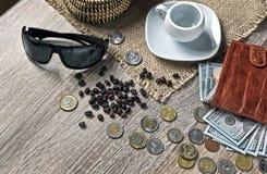 Κόκκινο πορτοφόλι με τα αμερικανικά δολάρια, τα διάφορα ξένα νομίσματα και το φλιτζάνι του καφέ στον πίνακα στοκ φωτογραφία