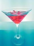 Κόκκινο ποτό κοκτέιλ με τους κύβους πάγου στο υπόβαθρο απόχρωσης πράσινου φωτός, τη διασκέδαση και το disco χορού Στοκ Φωτογραφίες