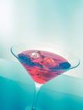 Κόκκινο ποτό κοκτέιλ με τους κύβους πάγου στο υπόβαθρο απόχρωσης πράσινου φωτός, τη διασκέδαση και το disco χορού Στοκ φωτογραφίες με δικαίωμα ελεύθερης χρήσης