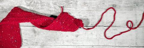 Κόκκινο πλεγμένο μαντίλι στον ξύλινο πίνακα, χειροτεχνία, επιγραφή Στοκ Εικόνες