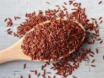 Κόκκινο ρύζι στο ξύλινο κουτάλι πέρα από το ξύλινο υπόβαθρο στοκ εικόνες