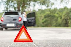 Κόκκινο σημάδι στάσεων έκτακτης ανάγκης με το θολωμένο αυτοκίνητο και γυναίκα που καλεί το αυτοκίνητο μ Στοκ εικόνες με δικαίωμα ελεύθερης χρήσης