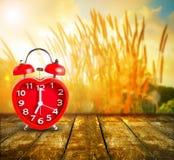 Κόκκινο σημάδι ρολογιών στο ρολόι 7 ο ` που τίθεται ξύλινο tabletop Στοκ Εικόνες
